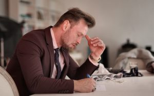 A man thinking deeply while writing on the table | Stay or Go?