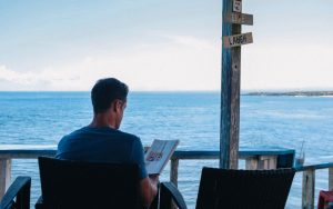 A man sitting on a chair and reading a magazine beside the beach | Top 10 Tips to Boost your Mental Health