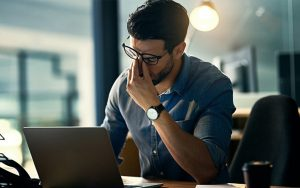 Man in front of his laptop holding on his nose | Well Being in the Workplace