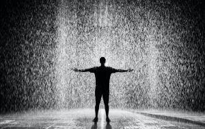 a dark silhouette of a man under the rain with his arms raised | When It Rains, It Pours. Or Does It?